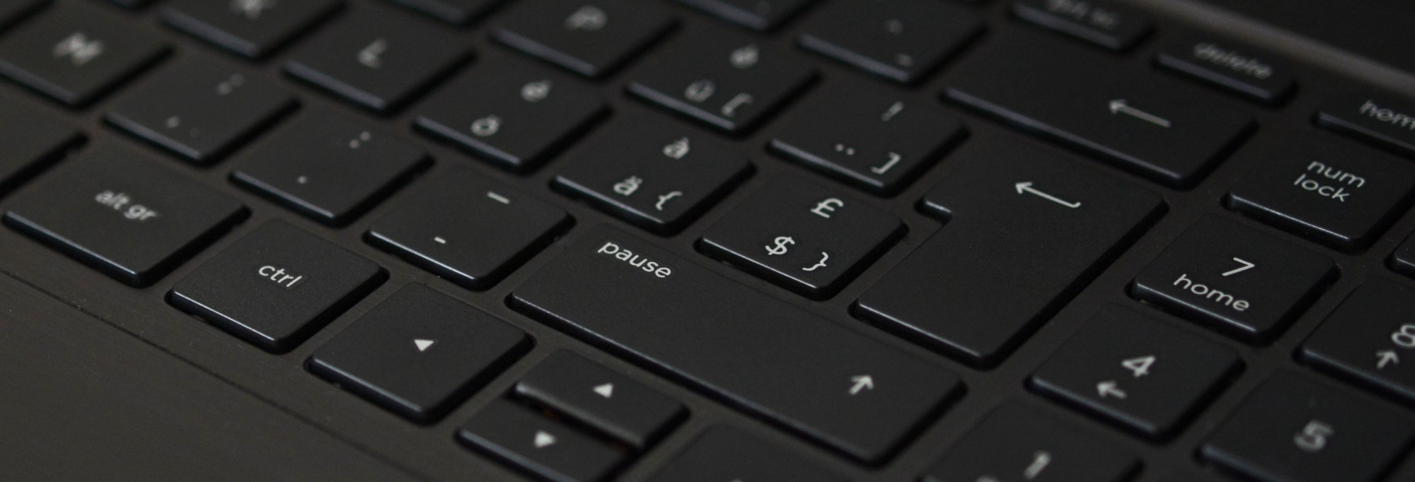 A close up, angled shot of a black computer keyboard